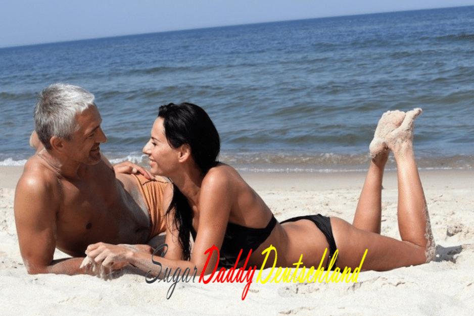 Reifer Mann und Sugarbaby sind glücklich und lächeln am Strand liegen.