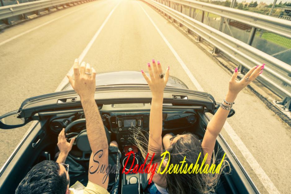 Mann und Frau heben in einem Cabrio die Arme und haben Spaß.