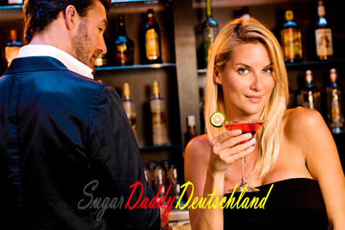 Junges Mädchen hat einen Drink mit einem Mann, der sie in einer Bar ansieht.